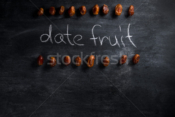 Date fruit over dark chalkboard background Stock photo © deandrobot