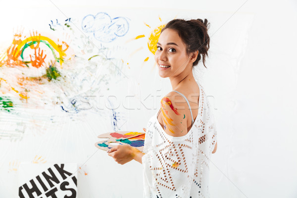 Happy young woman with palette and brushes painting Stock photo © deandrobot