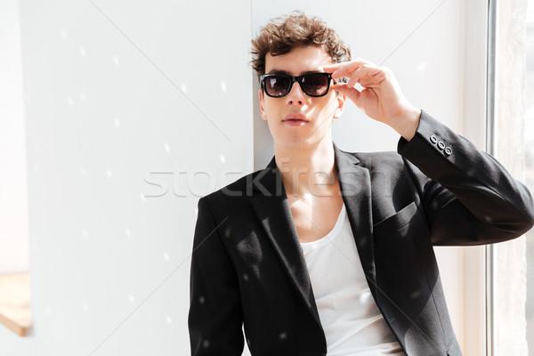 Uomo suit occhiali da sole seduta davanzale studio Foto d'archivio © deandrobot