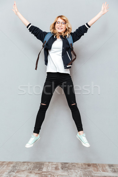 Happy young lady student wearing glasses with backpack jumping Stock photo © deandrobot