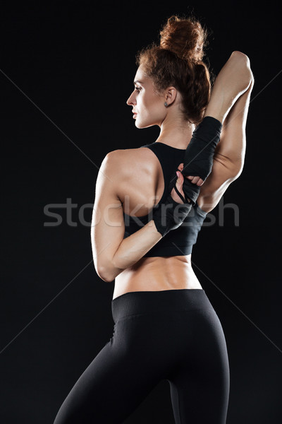Vertical image of female fighter warming up Stock photo © deandrobot