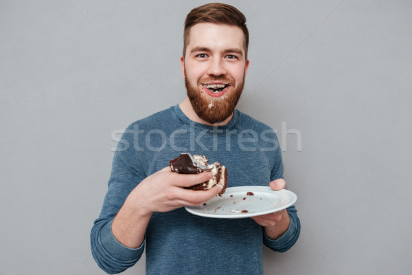 Mocskos szakállas fiatalember eszik krém torta Stock fotó © deandrobot