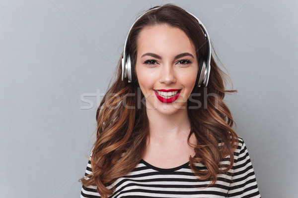 Smiling young lady standing over grey wall and listening music Stock photo © deandrobot