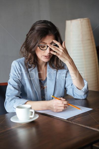 Thinking woman writer sitting indoors Stock photo © deandrobot