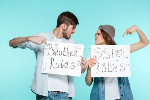 Stock photo: Handsome brother and pretty sister holding funny nameplates