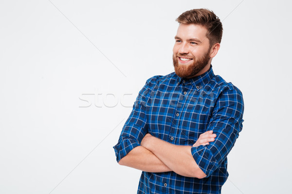Young bearded man with folded hands smiling to camera Stock photo © deandrobot