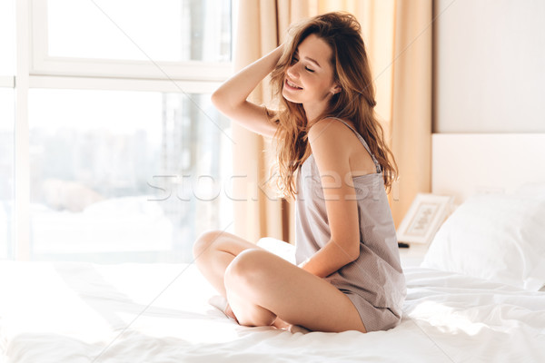 Pretty lady sitting on bed indoors Stock photo © deandrobot
