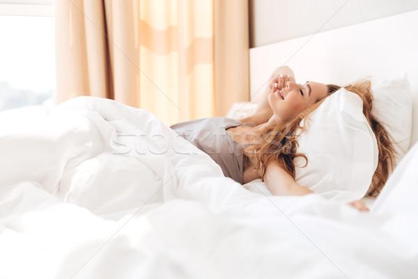 Glimlachend mooie dame bed binnenshuis Stockfoto © deandrobot
