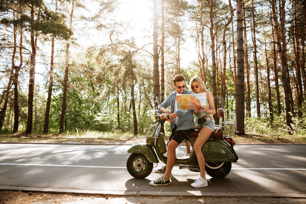 Happy loving couple holding map outdoors near scooter. Stock photo © deandrobot