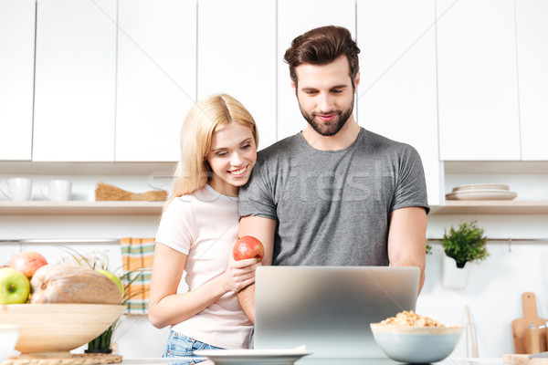 Young couple using laptop to look up recipe for their meal Stock photo © deandrobot