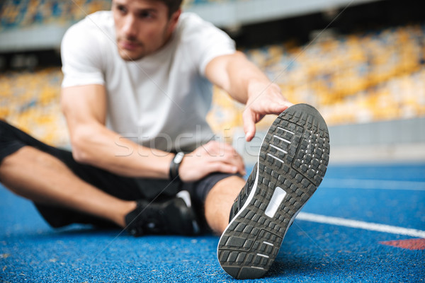 Stock photo: Young sports man at the stadium make stretching exercises.