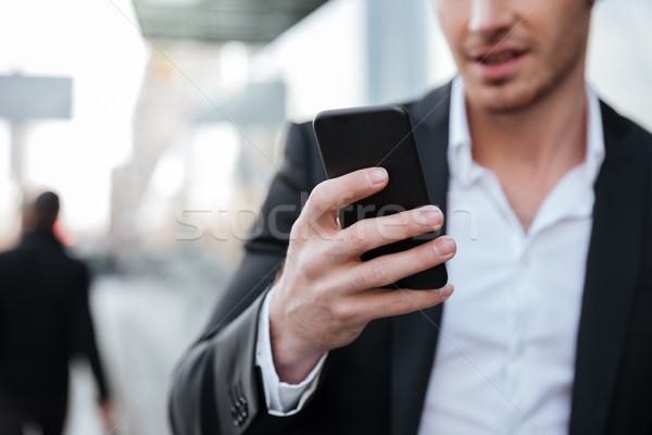 Cropped picture of happy young businessman chatting by phone. Stock photo © deandrobot