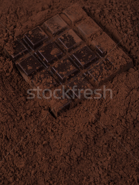 Dark chocolate bar covered in milk chocolate powder Stock photo © deandrobot