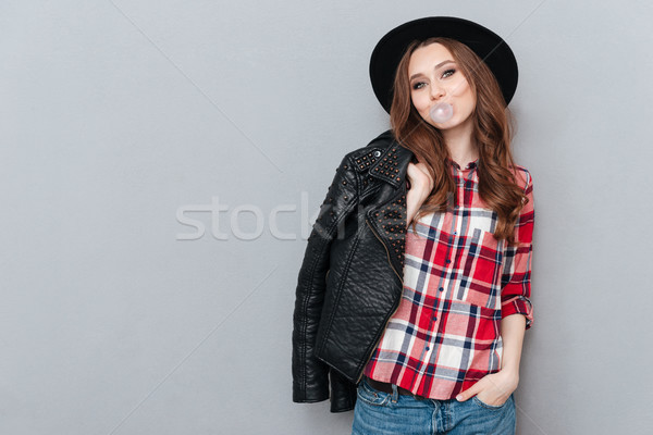 Young stylish girl wearing plaid shirt and chewing bubble gum Stock photo © deandrobot