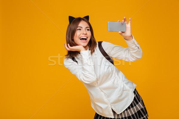 Feliz colegiala uniforme mochila posando Foto stock © deandrobot