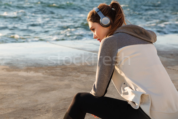 Photo of pretty sport woman listening to music, while resting af Stock photo © deandrobot