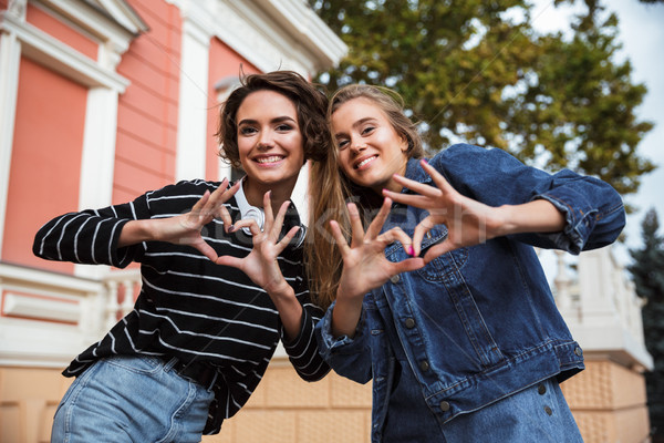 Two smiling happy teenage girls showing love gesture Stock photo © deandrobot