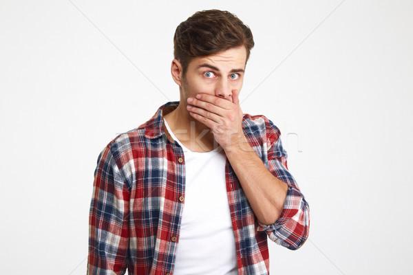 Portré meglepődött fiatalember befogja száját kéz néz Stock fotó © deandrobot