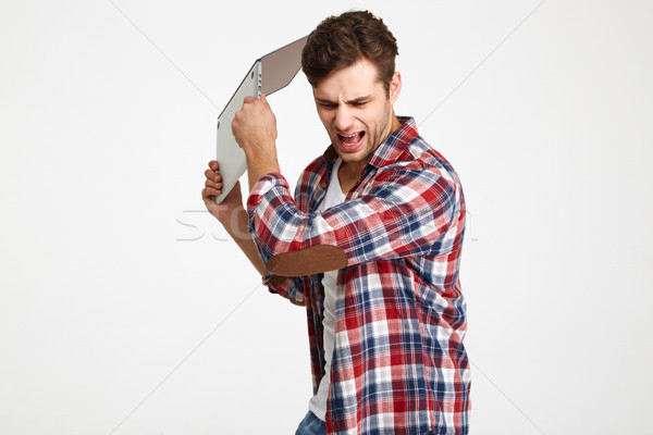 Portrait of an angry furious man throwing his laptop computer Stock photo © deandrobot
