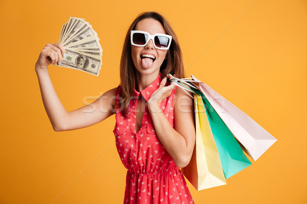 Funny female shopaholic holding fan of money and colorful shoppi Stock photo © deandrobot