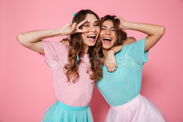 Two happy young woman in colorful clothes showing peace gesture, Stock photo © deandrobot