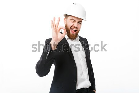 Happy bearded business man in protective helmet showing ok sign Stock photo © deandrobot