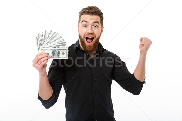 Cheerful bearded business man in shirt holding money Stock photo © deandrobot