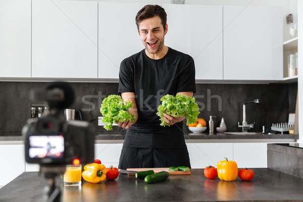 Cheerful young man filming his video blog episode Stock photo © deandrobot