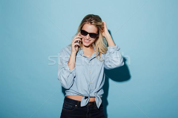 Gelukkig blonde vrouw shirt zonnebril praten smartphone Stockfoto © deandrobot