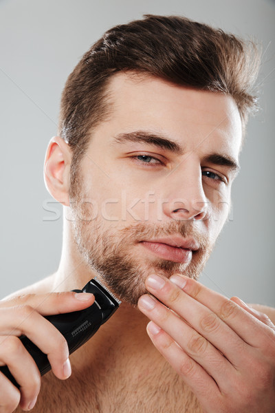 Young masculine male looking at camera being undressed and isola Stock photo © deandrobot