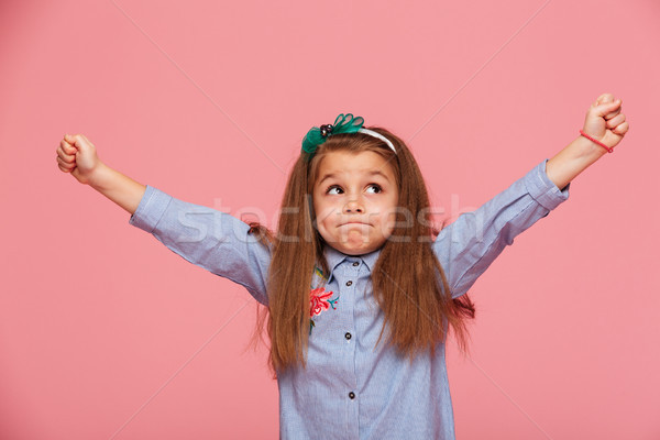 Cheerful little girl in hair hoop with pursed lips putting clenc Stock photo © deandrobot