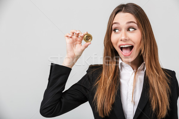 Photo of pretty businesswoman looking at golden bitcoin isolated Stock photo © deandrobot