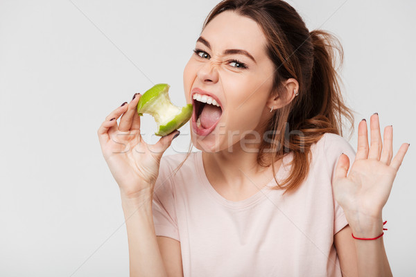 Close up portrait of a pretty girl biting an apple Stock photo © deandrobot