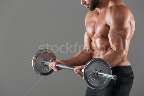 Side view cropped image of a strong shirtless male bodybuilder Stock photo © deandrobot