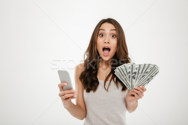 Portrait of attractive brunette female 30s winning lots of money Stock photo © deandrobot