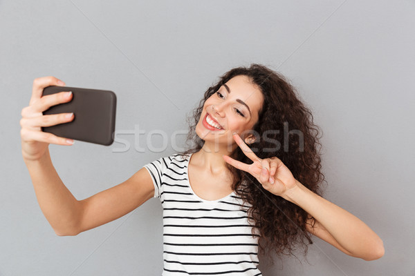 Amazing woman with caucasian appearance making selfie on her sma Stock photo © deandrobot