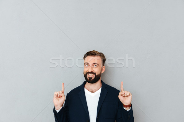Smiling bearded man in business clothes pointing and looking up Stock photo © deandrobot