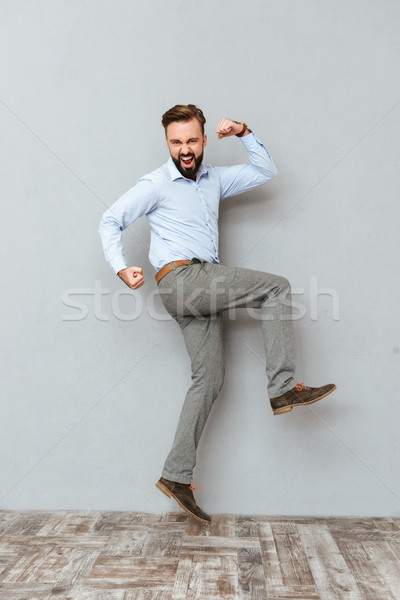 Full length image of screaming bearded man in business clothes Stock photo © deandrobot