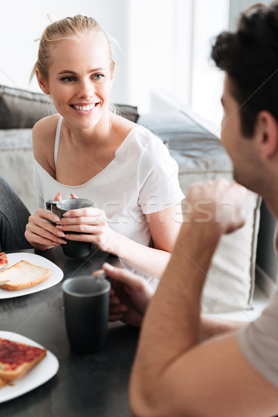 Attrcative cheerful lady looking at her man while they have breakfast Stock photo © deandrobot