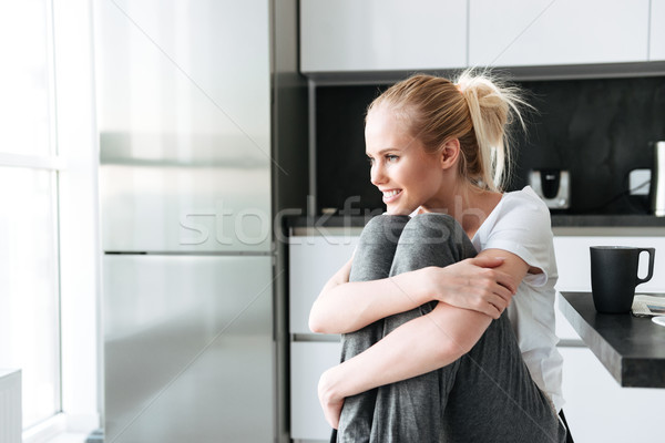 Smiling cute lady looking aside while sitting in kitchen Stock photo © deandrobot