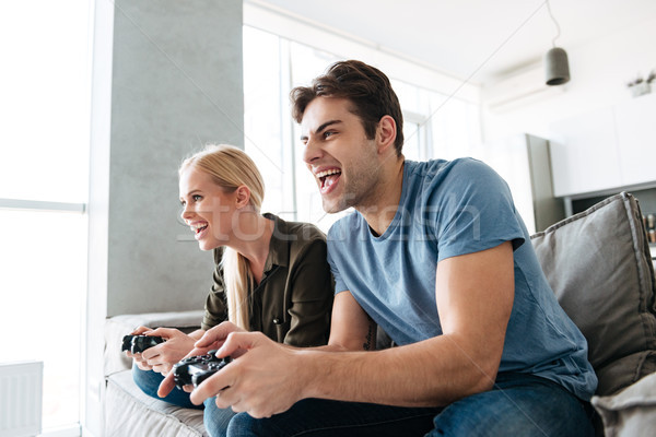 Young gambled lovers playing video games at home Stock photo © deandrobot