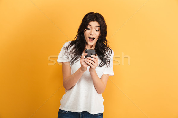 Emotional cute young pretty woman using mobile phone looking aside. Stock photo © deandrobot