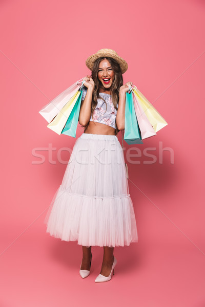 Full length image of shopaholic woman 20s wearing straw hat and  Stock photo © deandrobot