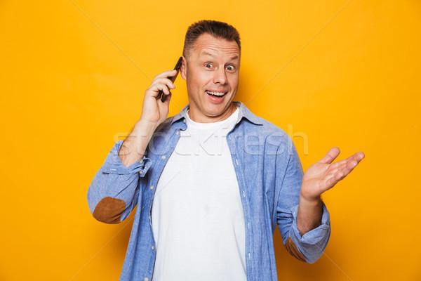Portré boldog középkorú férfi beszél mobiltelefon izolált Stock fotó © deandrobot