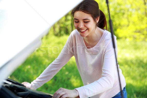 Smiling woman looks under hood car background green park Stock photo © deandrobot