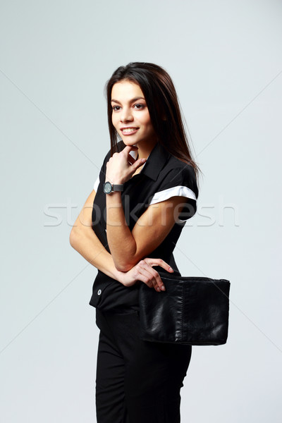 Young thoughtful woman standing in formal clothes on gray background Stock photo © deandrobot