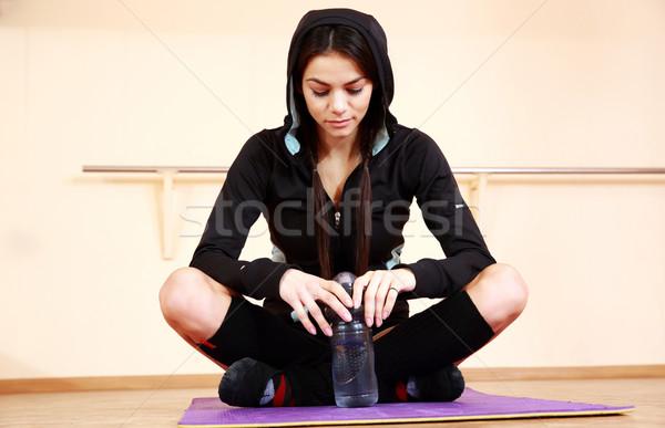 Genç dalgın uygun kadın oturma yoga mat Stok fotoğraf © deandrobot