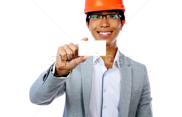 Young asian man with safety helmet holding blank card. Focus on card Stock photo © deandrobot