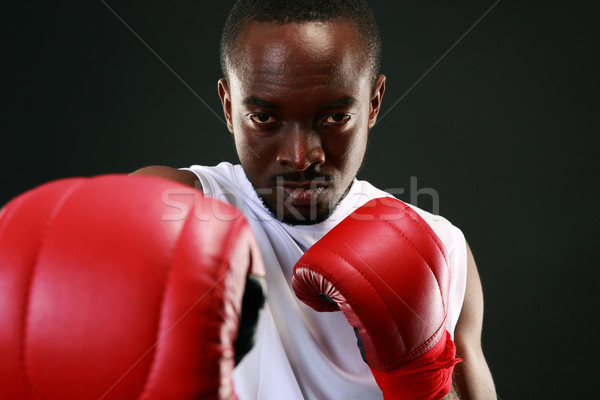 Portrait of an African American boxer punching in camera Stock photo © deandrobot