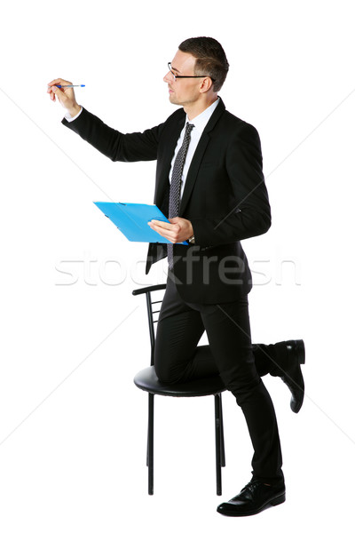 Confident businessman writes with pen at copyspace over white background Stock photo © deandrobot